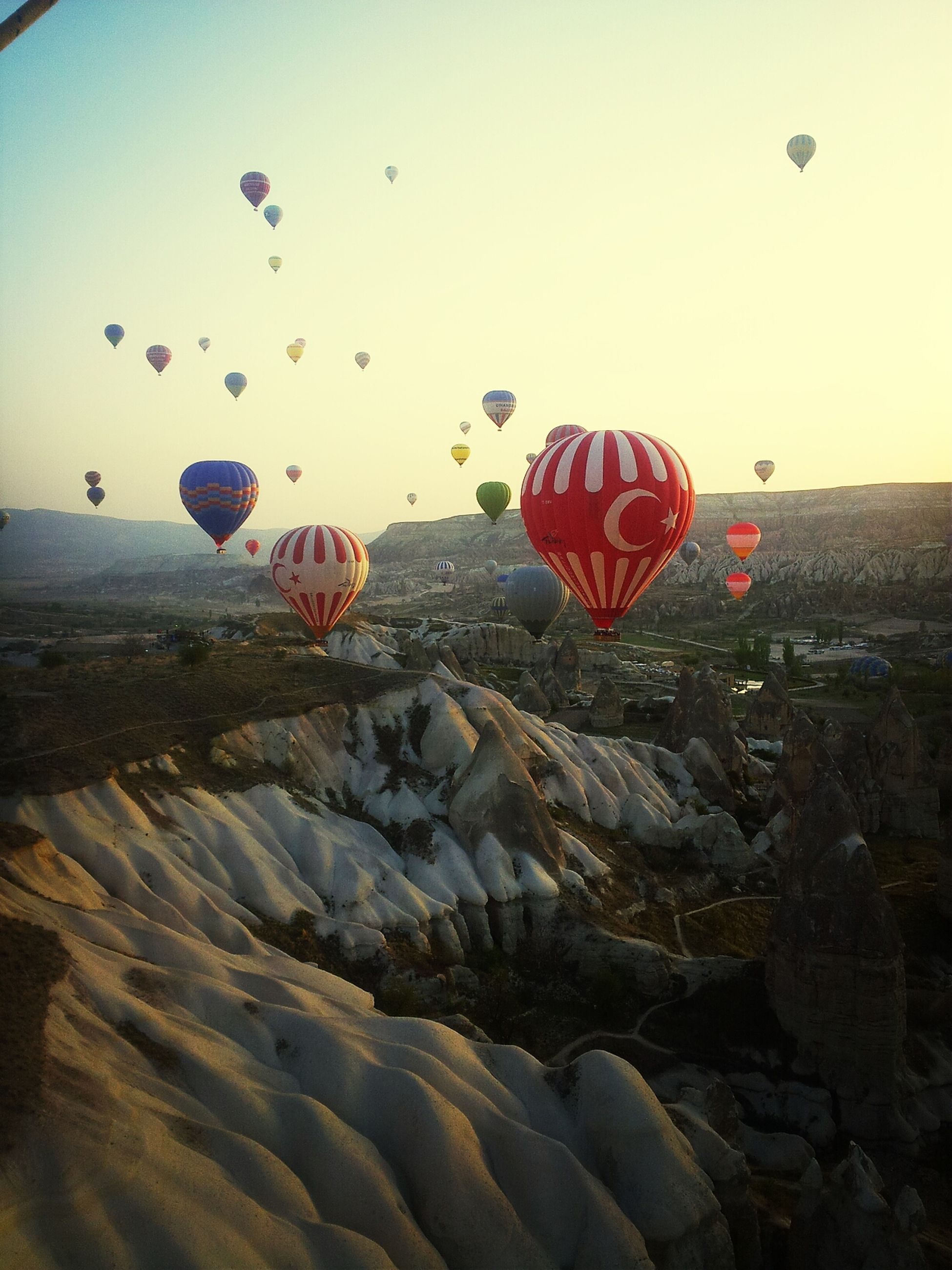 hot air balloon, mid-air, flying, sky, multi colored, parachute, clear sky, red, outdoors, flag, balloon, landscape, day, nature, sunlight, rock - object, no people, leisure activity, low angle view, celebration