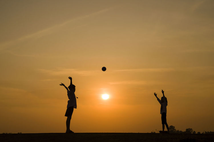 boy and girl playing ball in sunset Arms Raised Ball Beauty In Nature Full Length Human Arm Land Leisure Activity Lifestyles Men Mid-air Nature Orange Color Outdoors People Playing Real People Scenics - Nature Sea Silhouette Sky Standing Sun Sunset