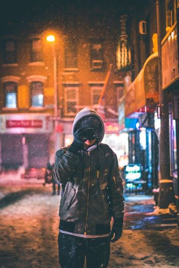 Man standing in city at night