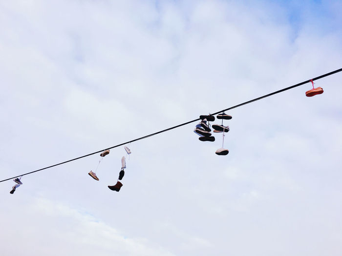 Low angle view of boots on the wire