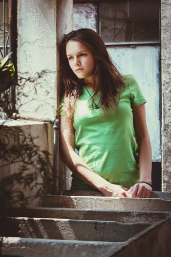 Beautiful young woman looking away while leaning on wall