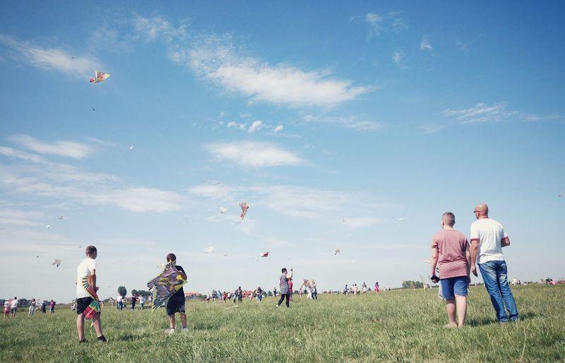 People flying kites on field against sky