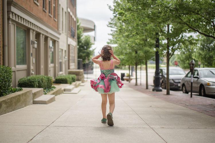 Full length rear view of woman walking in city