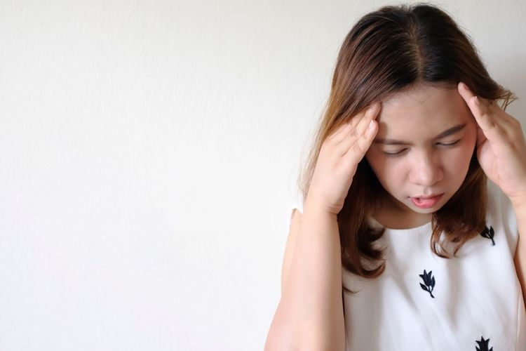 Young woman suffering from headache against white wall