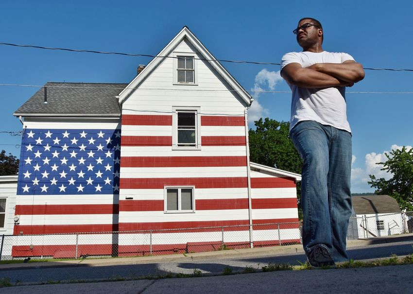 EyeEm Selects Patriotism Architecture Flag Building Exterior One Person Built Structure Real People Sunlight Day Lifestyles Full Length Leisure Activity Front View Casual Clothing Striped Blue Outdoors National Icon