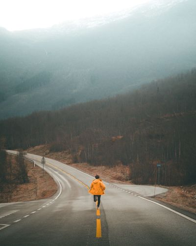 Rear View Of Man Running On Road Leading Towards Mountains