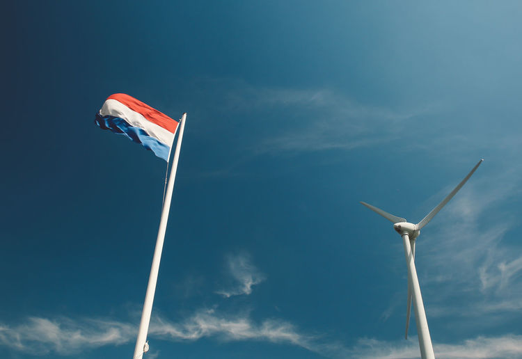 Low angle view of wind turbine and dutch flag against blue sky