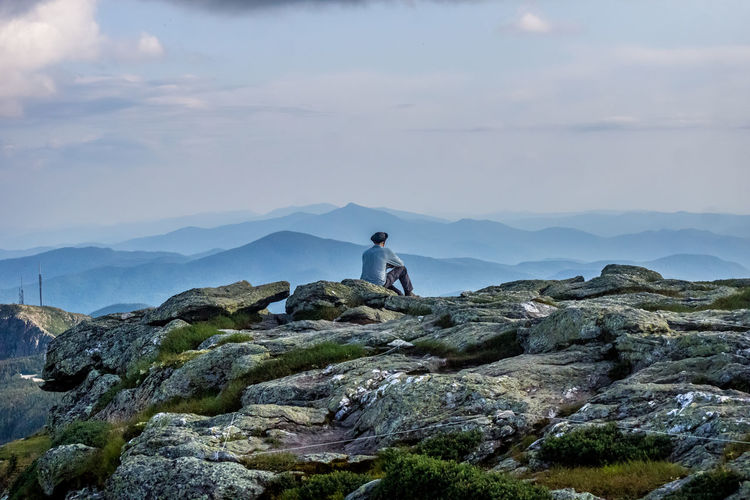 Rear view of man sitting on rock against mountains and sky