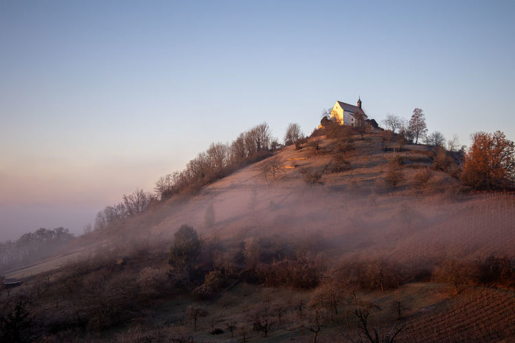 Chapel on mountain against clear sky