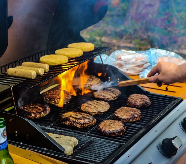 Close-up of person cooking food on barbecue