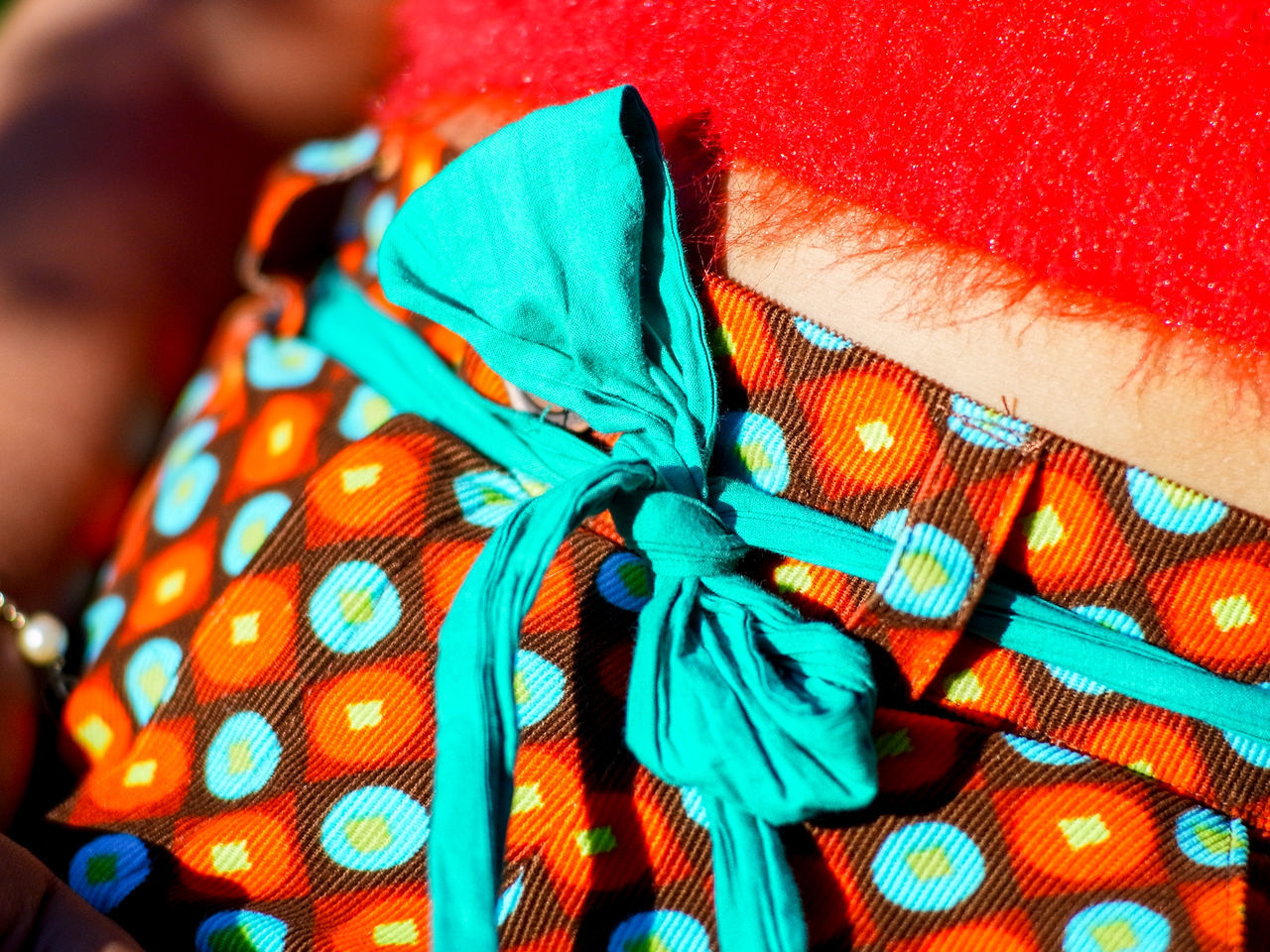 textile, close-up, indoors, pattern, no people, focus on foreground, multi colored, high angle view, clothing, blue, still life, fashion, body part, day, material, red, green color, turquoise colored, floral pattern