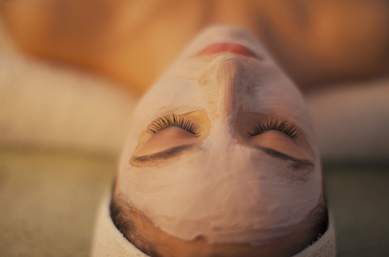 Close-up of woman with facial mask relaxing at beauty spa