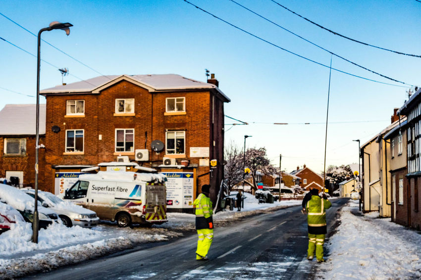 LEOMINSTER - DECEMBER 11: After a day of snow British Telecom engineers work to remove built up snow from over head cables in Leominster on December 11th 2017. British Telecom Workers Architecture Building Exterior Built Structure Cable City Clear Sky Day Outdoors Residential Building Road Sky Street
