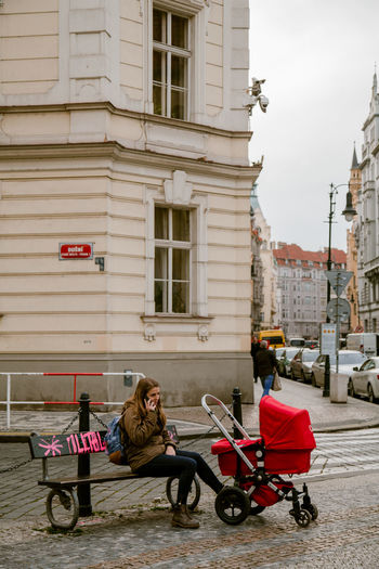 Baby Stroller Stroller Mother Young Mother On Phone Portrait Of A Woman Streetphotography Street Photography Prague City Street Building Exterior Architecture Built Structure Bench Park Park Bench Baby Carriage