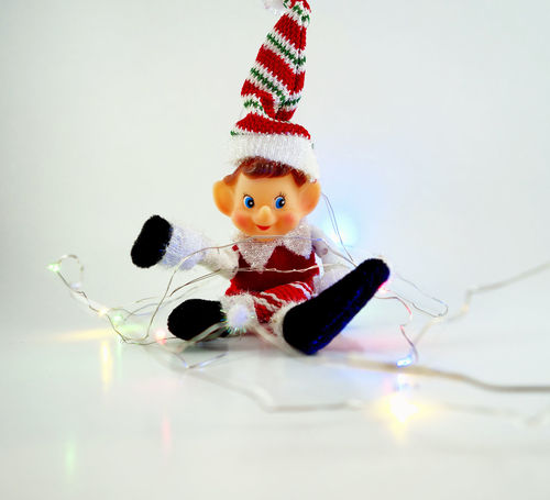 Elf untangles Christmas lights. Christmas Christmas Elf Christmas Lights Elf Holiday Japan Winter Childhood Childhood Memories Christmas Holidays Close-up Mischievous No People Red And Green Studio Shot Vintage White Background