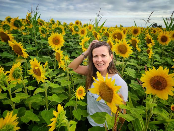 Portrait of smiling woman with sunflower in field