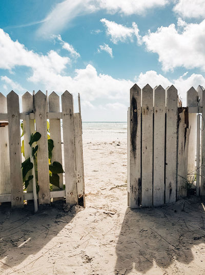 White fence and door leading to paradise sandy beach. sea, vacation, no people.