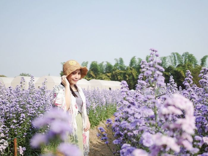 Woman standing on purple flowering plants on field against sky