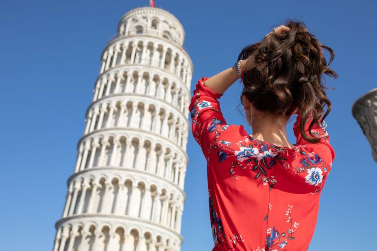 Woman standing against leaning tower of pisa