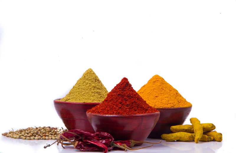 Close-up of various spices in bowls on white background