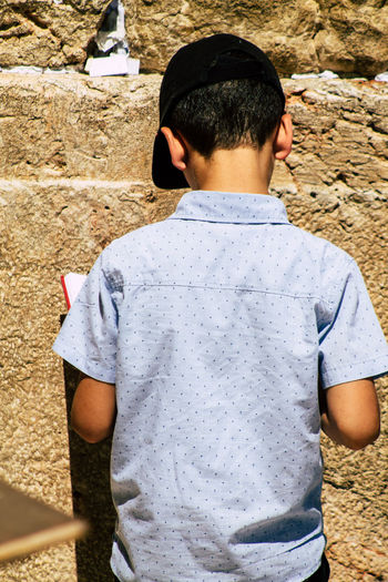 Rear view of boy standing on land