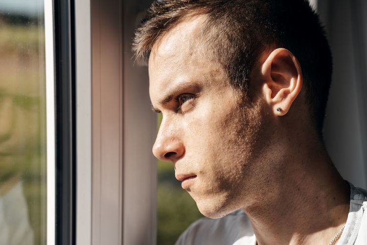 Young man looks out of window hopeful and daydreaming