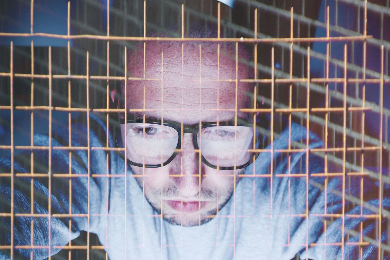 Double exposure of mid adult man with metal fence