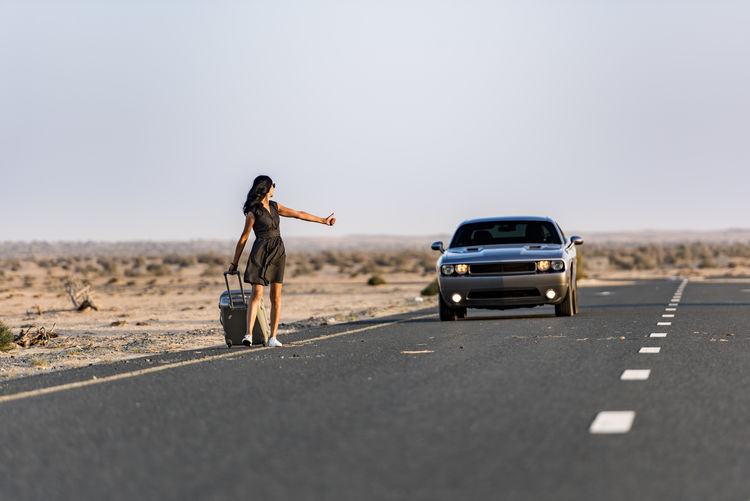 Woman hitch hiking on rural road in the desert with her luggage and a sport car coming behind her Desert Adult Car Casual Clothing Clear Sky Copy Space Day Full Length Girl Hitchhiking Leisure Activity Mode Of Transportation Motor Vehicle Nature One Person Outdoors Road Roadtrip Sky Standing Transportation Travel Vehicle Breakdown Women Young Adult