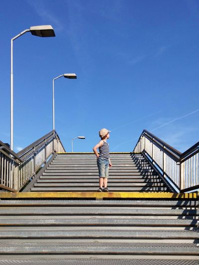 Boy standing on steps against clear sky