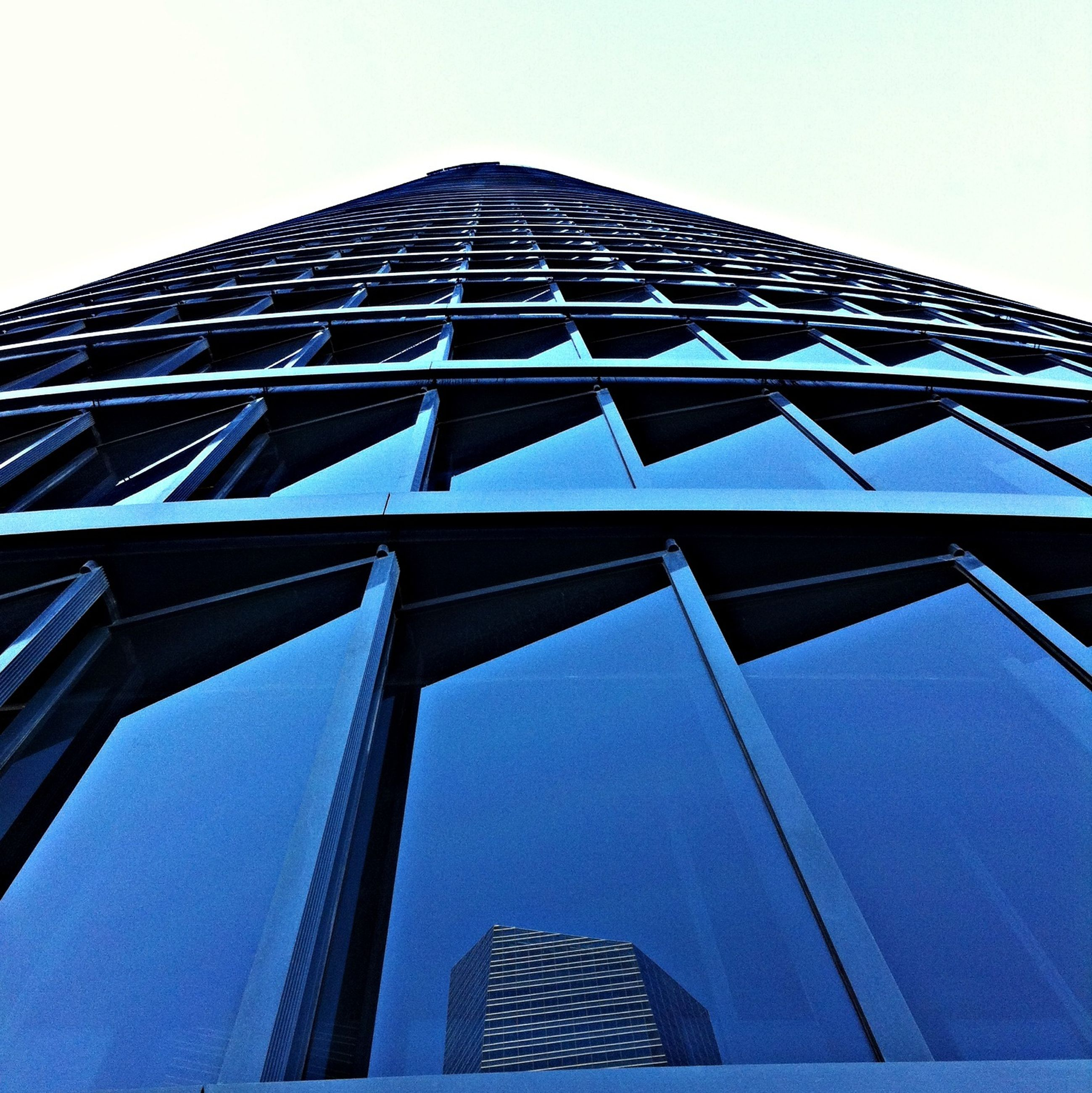 low angle view, architecture, building exterior, built structure, modern, office building, skyscraper, tall - high, city, tower, building, glass - material, clear sky, reflection, sky, window, day, tall, no people, outdoors