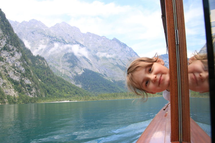 Portrait of girl on boat by mountains