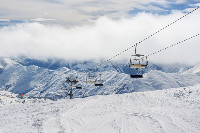 An empty chairlift on the background of snow-covered ridges tightened