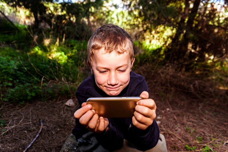 Boy using mobile phone outdoors