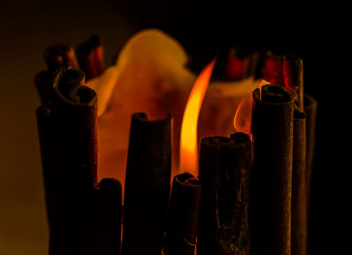 Close-up of fire amidst cinnamon sticks