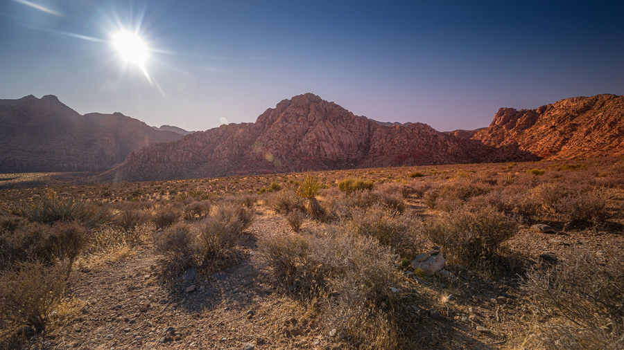 Scenic view of mountains against bright sun