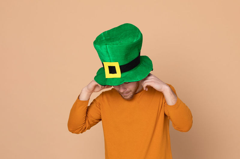 Man wearing green hat standing against beige background