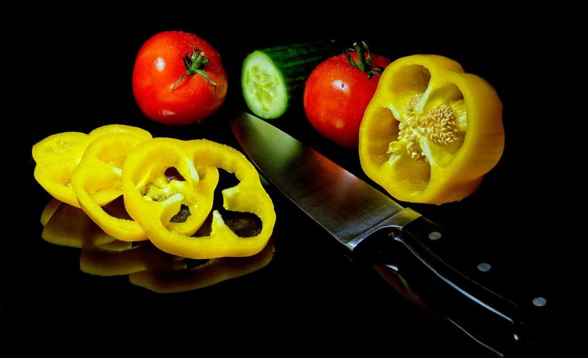 High angle view of chopped fruits against black background