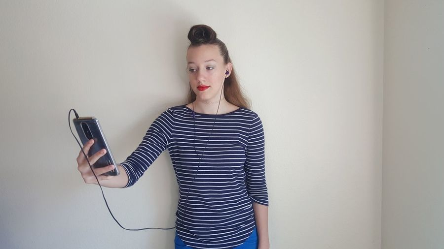 Teenage Girl Listening To Music While Using Phone Against Wall