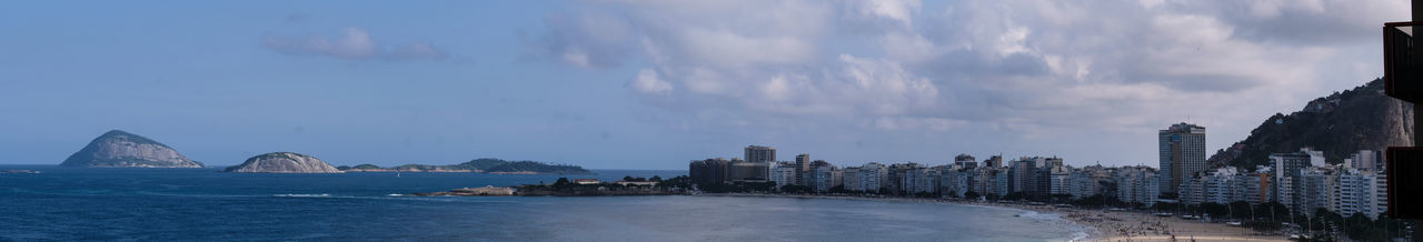 Panoramic view of city buildings against cloudy sky