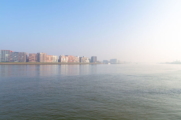 Misty morning on the river Beneden Merwede between Dordrecht and Papendrecht in The Netherlands Papendrecht Apartment Architecture Beautiful Beneden Merwede Blue Sky Boat Bright Building Buildings Calm Construction Copy Space Crossing Day Design Dordrecht Dutch Europe European  Ferry Flat Flats Hazy  Holland Homes House Landmark Landscape Mist Misty Modern Morning Netherlands Nobody Panorama Quiet Reflection Residential  River Riverside Sky Skyline Still Sunny Day Town Travel Urban View Water Building Exterior Built Structure Waterfront City Sea Nature No People Clear Sky Outdoors Cityscape Office Building Exterior Skyscraper Tranquility