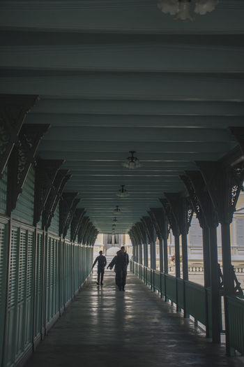 Rear view of people walking on footpath amidst buildings