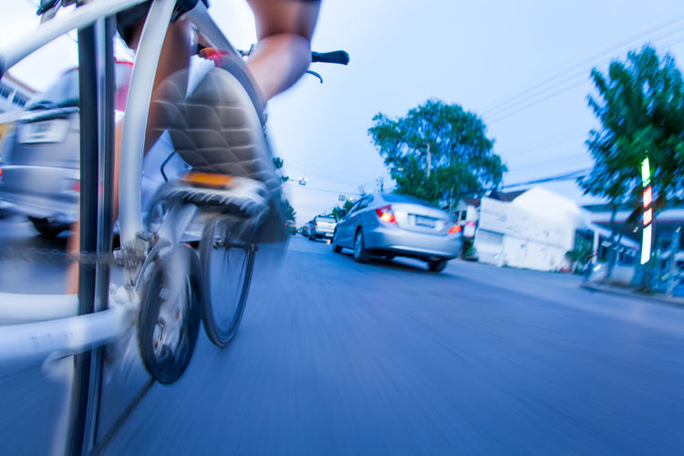 Low section of woman riding bicycle on road in city