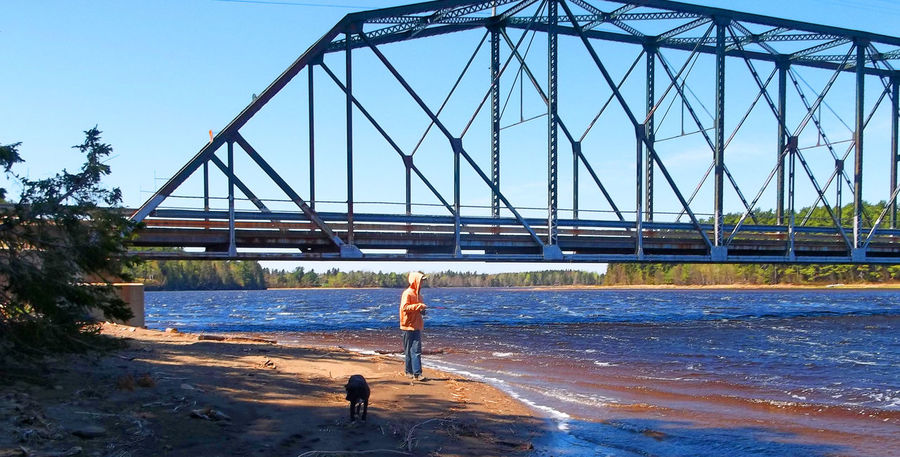 Boy and dog, fishing at old steel bridge on the river Boy Boy And Dog Boy Fishing Boyhood Bridge - Man Made Structure Built Structure Clear Sky Day Fishing Fishing Time Full Length Heartwarming Leisure Activity Lifestyles Nature One Person Outdoors Rear View River Riverview Sky Steel Bridge Sunlight Water Young Adult