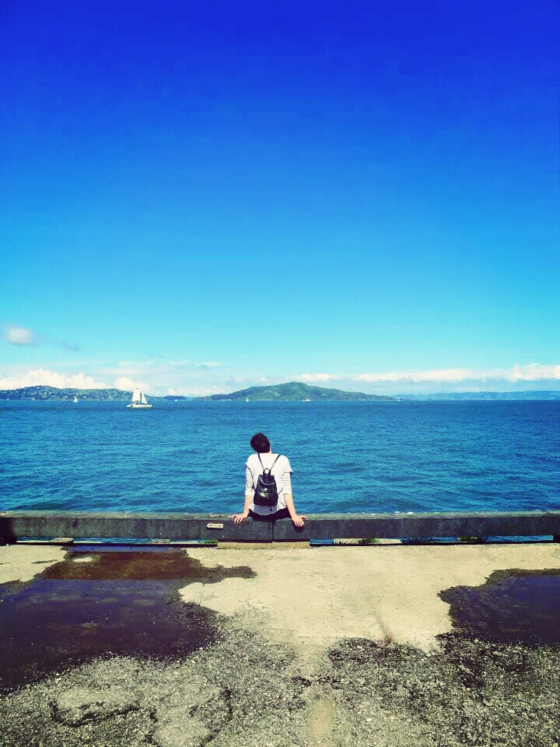 sea, water, horizon over water, blue, clear sky, sitting, relaxation, tranquility, tranquil scene, copy space, scenics, leisure activity, lifestyles, rear view, beach, beauty in nature, nature, shore