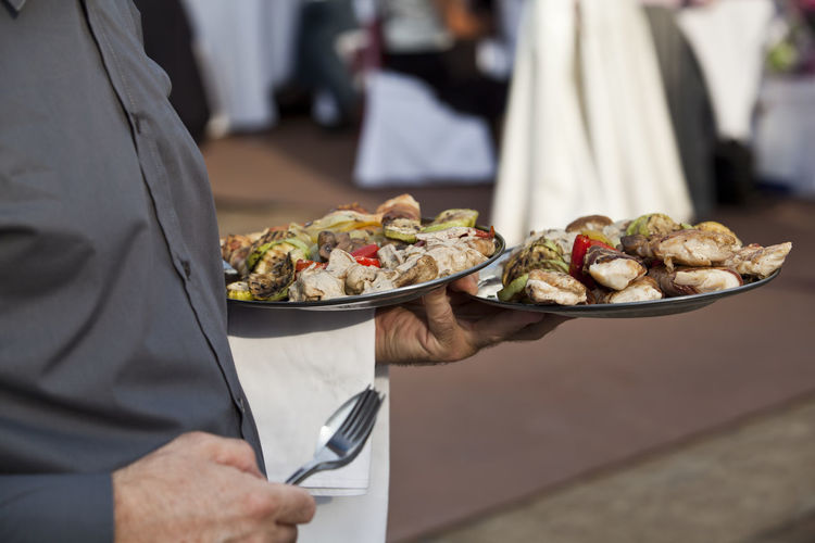 A waiter carrying plates of food at a party Celebration Eating Event Reception Wedding Catering Enjoyment Focus On Foreground Food Food And Drink Grilled Meat Grilled Vegetables Holding Leisure Time Party Party - Social Event Plate Ready-to-eat Serve Serving Serving Tray Spoon And Fork Tray Waiter Wellbeing