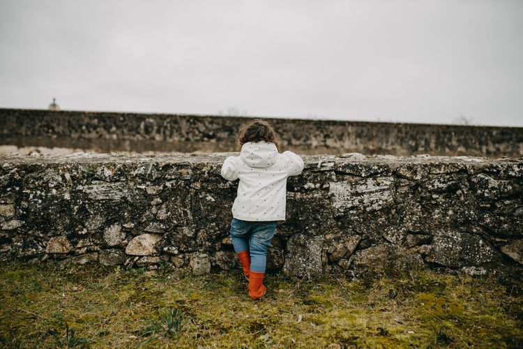 Rear view of girl standing by stone wall against sky