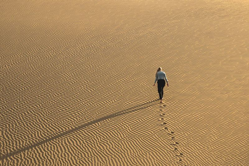 High angle view of woman walking on sand at desert