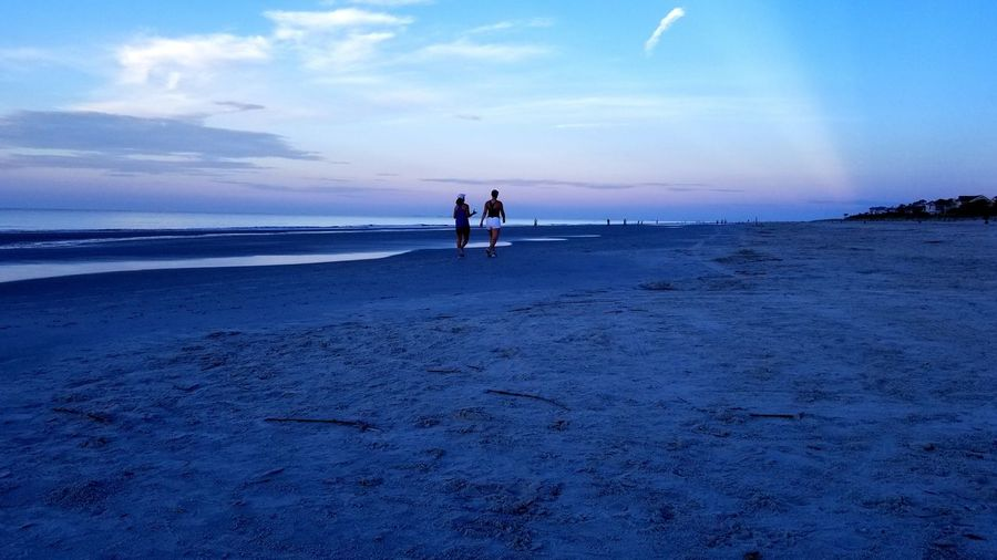 Rear view of people walking at beach against sky during sunset