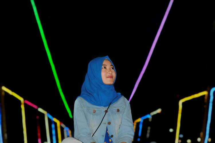 Young Woman At Amusement Park During Night