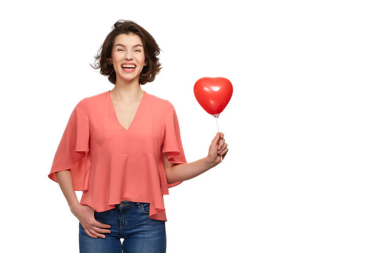 Woman standing with balloons against white background